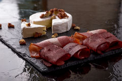 Cheese camembert with walnuts and meat plate with walnuts on black slate plate background. Stock Photos