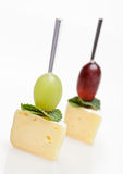 Cheese canape with grape and mint on white. Two Cheese canape with grape and mint isolated on white royalty free stock photography
