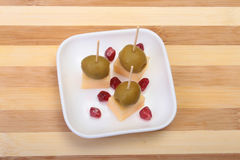 Cheese canapes with olives and Grains of pomegranate on wooden tray close up. Royalty Free Stock Images