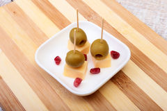 Cheese canapes with olives and Grains of pomegranate on wooden tray close up. Royalty Free Stock Image