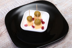 Cheese canapes with olives and Grains of pomegranate on wooden tray close up. Stock Photography