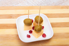 Cheese canapes with olives and Grains of pomegranate on wooden tray close up. Stock Image