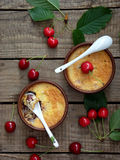 Cheese casserole or crumble with cherries in brown cup. On wooden background stock photo