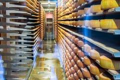 Gruyere cheese matures at the wooden shelfs, Gruyeres, Switzerland. Royalty Free Stock Images