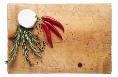 Cheese and chilli on a cutting board. Wooden cutting board with cheese, rosemary and chilli, top view Stock Image