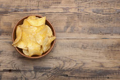 Cheese and chive potato crisp snack in brown bowl on wooden back Stock Photo
