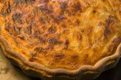Cheese and Chive Quiche. Lovely brown cooked quiche on blackened baking tray Stock Photo