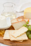 Cheese with cookies, grapes and white wine. On wooden desk royalty free stock photography