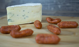 Cheese corner with Salamis. A corner of cheese on a wooden tray with some small Salamis Royalty Free Stock Images