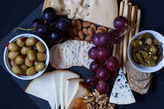 Cheese,cracker,grape,nuts on a black background Royalty Free Stock Photo
