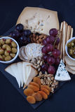 Cheese,cracker,grape,nuts on a black background Royalty Free Stock Photos