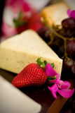 Cheese and crackers. An appetizer selection of cheese, crackers, grapes and strawberries Stock Photography