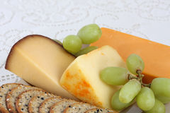 Cheese and crackers. Selection of cheese and crackers with green grapes with lace tablecloth background Stock Photo