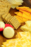 Cheese and crackers. Assortment of cheeses and crackers on a wood server Royalty Free Stock Photography