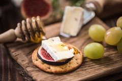 Cheese crackers with camembert and fresh fig and honey Royalty Free Stock Images