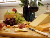 Cheese and crackers with grapes and wine. Selection of cheese and crackers with wine and grapes in the background Stock Image