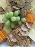 Cheese & Crackers. Green grapes adorn a plate of assorted cheese & crackers for the holidays Royalty Free Stock Photos