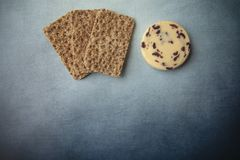 Cheese and crackers on blue background. Cheese with cranberry and crackers on blue background stock image