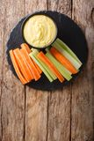 Cheese creamy dip sauce with fresh celery and carrots close-up. Cheese creamy dip sauce with fresh celery and carrots close-up on the table. Vertical top view Royalty Free Stock Images