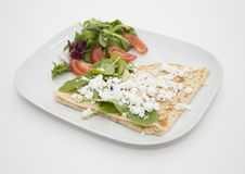 Cheese crepe with salad. Crepe covered with feta cheese and green salad on white china plate Stock Photography