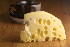 Cheese and cup. Piece of cheese close-up and dark cup on brown wood surface Royalty Free Stock Images