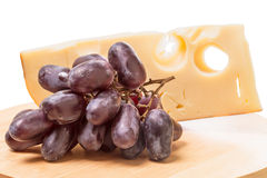Cheese and dark grapes Stock Images