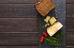 Cheese delikatessen with bread on black stone, parmesan Royalty Free Stock Photo
