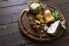 Cheese delikatessen on rustic wood, blue roquefort, brie and parmesan Stock Photo