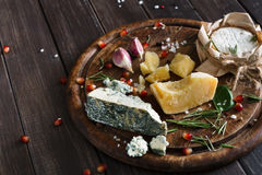 Cheese delikatessen on rustic wood, blue roquefort, brie and parmesan Royalty Free Stock Photos