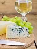 Cheese different with grapes and wine on the board Stock Images