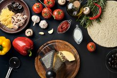 Cheese, different vegetables on black table. Ingredients for traditional italian pizza. stock image
