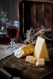 Cheese, dread and red wine on a wooden background, rustic style.  Stock Photo