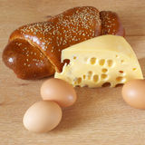 Cheese, eegs and bun. Piece of cheese, eggs, and bun on beige wood surface Royalty Free Stock Photo