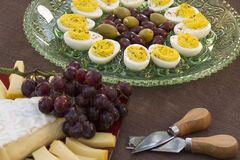 Cheese, Eggs, Olive and Grapes. Deviled eggs, kalamata and green olives with brie and Gouda and grapes served as horderves before dinner Stock Image