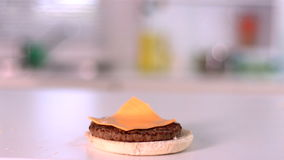 Cheese falling on bun burger in kitchen stock video