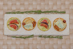 Cheese and figs on crackers on placemat Stock Photography