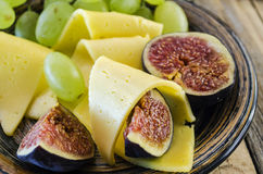 Cheese with figs and grapes Stock Photography