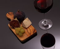 Cheese, figs and grapes on cutting board Stock Image
