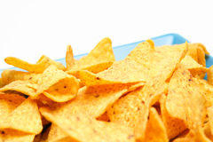 Cheese Flavored Chips. Some cheese flavored tortilla/Nacho chips on a large snack plate on white background. Shallow DOF, focus on the middle part of the chips Royalty Free Stock Photo