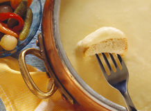 Cheese fondue. White bread on a fork in a cheese sauce Stock Photography
