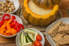 Cheese fondue in a roasted pumpkin with bread and vegetables Stock Photography