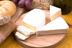 Cheese and food. Macro image of cheese, bread, grapes and wine on wooden table stock photos