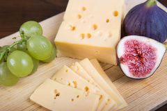 Cheese and fresh figs on the wooden cutting board Royalty Free Stock Photos