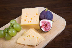 Cheese and fresh figs on the wooden cutting board Stock Images