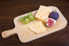 Cheese and fresh figs on the wooden cutting board Royalty Free Stock Photography