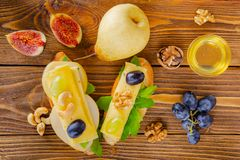 Cheese, fruit and honey. Tool for cheese. Wooden table. View fro royalty free stock photo