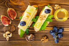 Cheese, fruit and honey. Tool for cheese. Wooden table. View fro stock images