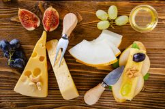 Cheese, fruit and honey. Tool for cheese. Wooden table. View fro. Cheese, fruit and honey. Tool for cheese. Wooden table. Top view stock photos