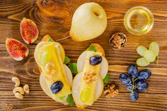 Cheese, fruit and honey. Tool for cheese. Wooden table. View fro. Cheese, fruit and honey. Tool for cheese. Wooden table. Top view royalty free stock photo