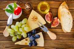 Cheese, fruit and honey. Tool for cheese. Wooden table. stock photo
